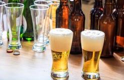 Un contatore di legno del pub, fuoco su due vetri pieni di birra Immagini Stock Libere da Diritti