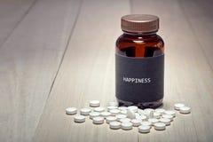 Un contenitore della droga con l'etichetta nera scritta felicità su  fotografia stock