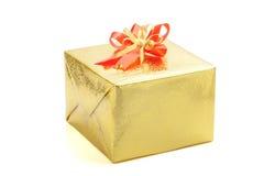 Un contenitore di regalo dell'oro con l'arco rosso del nastro su fondo bianco, nuovo sì Immagini Stock Libere da Diritti