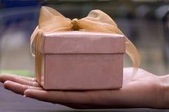 Un contenitore di regalo sulla mano della ragazza Fotografia Stock
