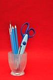 Un contenitore di vetro con le forbici e le matite immagini stock