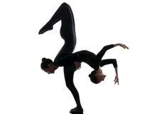 Un contorsionista di due donne che esercita la siluetta relativa alla ginnastica di yoga Fotografie Stock