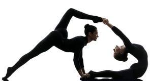 Un contorsionista di due donne che esercita yoga relativa alla ginnastica Immagine Stock