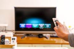 Un control de la mano de las mujeres el teledirigido de la caja de la TV en la sala de estar, la pantalla negra TV Foto de archivo libre de regalías