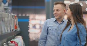 Un control del hombre y de la mujer en sus manos una caldera eléctrica en una tienda que elige antes de comprar en tienda de dis metrajes