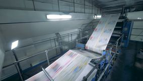 Un convoyeur relève des feuilles à une imprimerie, fin banque de vidéos