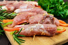 Un-cooked, pork meat rolls stuffed with vegetables pepper, carrots in hot garlic sauce on a cutting board. Stock Images