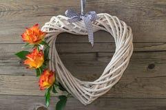 Un corazón blanco hecho de vid, adornado con las rosas anaranjadas hermosas Foto de archivo libre de regalías