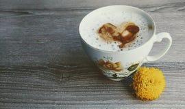 Un corazón de c4offee en la leche La taza hermosa con la flor amarilla en ella y le acerca Fondo de madera fotos de archivo libres de regalías