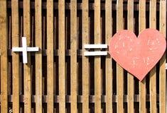 Un corazón de madera del color rojo hecho de la madera simboliza amor fotografía de archivo