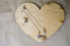 Un corazón de madera para el día del ` s de la tarjeta del día de San Valentín con los pendientes de plata con los diamantes, pie fotos de archivo libres de regalías