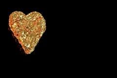 Un corazón de oro en izquierdo. Fotografía de archivo libre de regalías