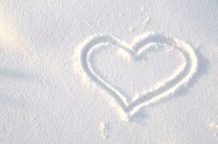 Un corazón dibujado en la nieve foto de archivo