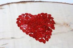 Un corazón grande hecho de pequeños corazones en un tablero de madera Foto de archivo