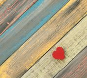 Un corazón rojo en un fondo de madera diagonal del tablón Imagen de archivo libre de regalías
