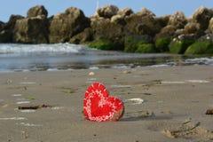 Un corazón rojo en la arena delante de las rocas imagen de archivo libre de regalías