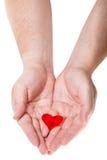 Un corazón rojo en las palmas masculinas aisladas Imagen de archivo