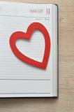 Un corazón rojo en una página de la lechería para el 14 de febrero Imagen de archivo
