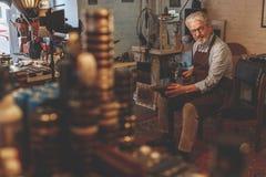 Un cordonnier plus âgé dans l'atelier photos libres de droits