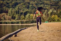 Un corredor de la muchacha de los deportes corre a lo largo de la orilla del lago que activa Imagen de archivo libre de regalías