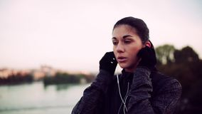Un corredor femenino joven del ajuste que se coloca al aire libre en el puente en la ciudad, poniendo en los auriculares almacen de video