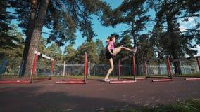 Un corridore femminile salta sopra un ostacolo Riscaldamento prima di correre video d archivio