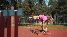 Un corridore femminile salta sopra un ostacolo Riscaldamento prima di correre archivi video