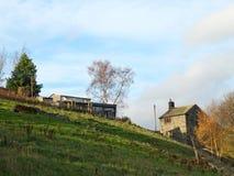 Un cortijo de piedra viejo y vertientes en la cima de un prado verde de la ladera con los ?rboles y las paredes de piedra en el c imagen de archivo libre de regalías