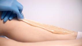 Un cosmetólogo de sexo femenino del doctor aplica la goma del azúcar en la piel de las piernas del ` s del cliente fotografía de archivo