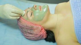 Un cosmetólogo en guantes quita una máscara de la arcilla de una cara de la mujer s con un cojín de algodón Vista lateral almacen de metraje de vídeo