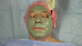 Un cosmetólogo femenino en guantes pone una cara de un cliente masculino una máscara del fango con un cepillo almacen de video