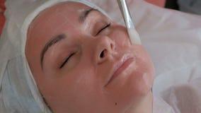 Un cosmetologist aplica el gel blanco a una cara roja de una muchacha en un salón de belleza con un cepillo blanco Primer de almacen de video