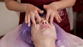 Un cosmetologist de femme applique une crème thérapeutique spéciale au visage du patient Peau propre, soin banque de vidéos