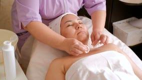 Un cosmetologist femenino profesional frota el cuello y el escote del cliente con los cojines de algodón mojados Muchacha asiátic metrajes