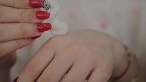Un cosmetologist profesional aplica la crema nana en las manos para el masaje facial Nuevo concepto en cosmetología almacen de video
