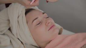 Un cosmetologist profesional aplica una mascarilla a una chica joven con un cepillo Nuevo concepto en cosmetología almacen de metraje de vídeo