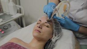 Un cosmetologist profesional hace un vacío de la mujer que limpia la cara en un salón de belleza Innovaciones de Cosmetological almacen de video