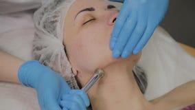 Un cosmetologist profesional hace un vacío de la mujer que limpia la cara en un salón de belleza Innovaciones de Cosmetological metrajes