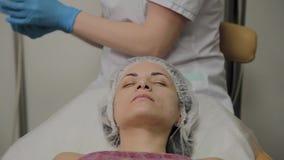 Un cosmetologist profesional hace un vac?o de la mujer que limpia la cara en un sal?n de belleza Innovaciones de Cosmetological almacen de video