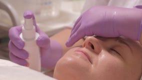 Un cosmetologist professionnel dans les gants lilas avec des couvertures d'une main ses yeux, tandis que les autres pulvérisateur images stock
