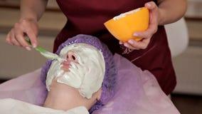 Un cosmetologo con esperienza prepara una maschera sana per il cliente Si alza e tocca il fronte con una spazzola a archivi video
