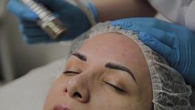 Un cosmetologo professionale fa un vuoto della donna che pulisce il fronte in un salone di bellezza Innovazioni di Cosmetological video d archivio