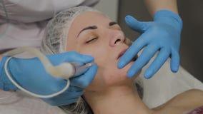 Un cosmetologo professionale fa un vuoto della donna che pulisce il fronte in un salone di bellezza Innovazioni di Cosmetological archivi video