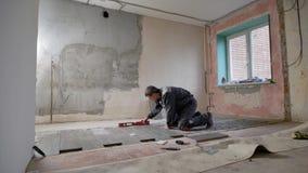 Un costruttore che lavora nei posti di abitazione le mattonelle sul pavimento e controlla il pendio e l'uguaglianza del pavimento