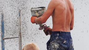 Un costruttore maschio applica la rifinitura decorativa con uno spruzzatore intonacante su una parete della via video d archivio