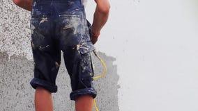 Un costruttore maschio applica la rifinitura decorativa con uno spruzzatore intonacante su una parete della via stock footage