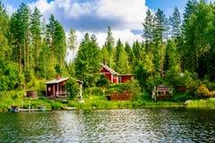 Un cottage di legno finlandese tradizionale con una sauna e un granaio sul lago puntellano Estate Finlandia rurale fotografia stock
