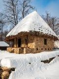 Un cottage en pierre avec un toit couvert de chaume couvert dans la neige Images stock