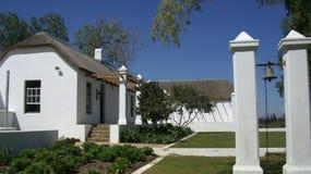 Un cottage en pierre blanc avec le toit tubulaire Photo stock