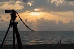 Un coucher du soleil au-dessus de l'océan avec des personnes appréciant la vue Photo stock